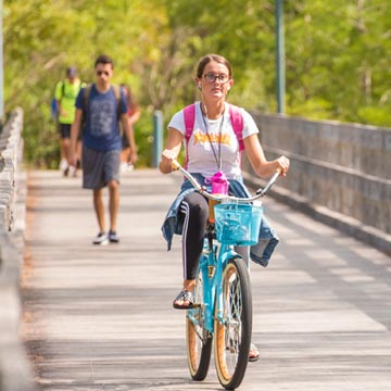 Student riding across bridge