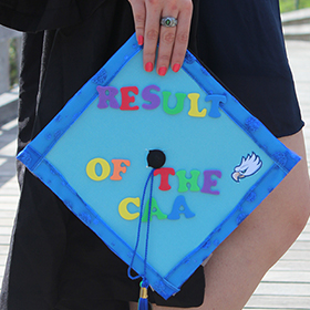 student holding a cap