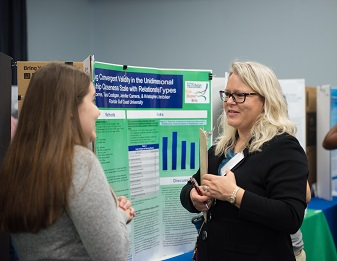 Student presenting research poster to a faculty member