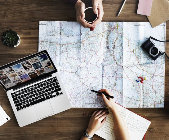 person planning out travles on a map with friend