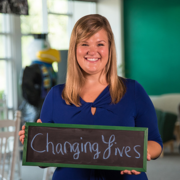 Teacher Holding Changing Lives sign
