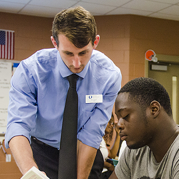 fgcu student teaching a high school student