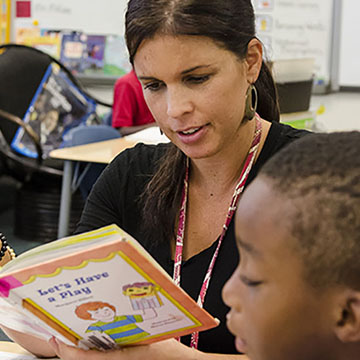 teacher reading to young boy