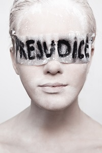 Woman with eyes covered with sign that reads Prejudice