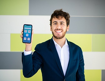 Jack Hellmer holding phone displaying screen of the app he is building