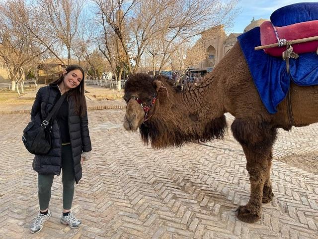 Carolyne Mesa in Uzbekistan with a camel.