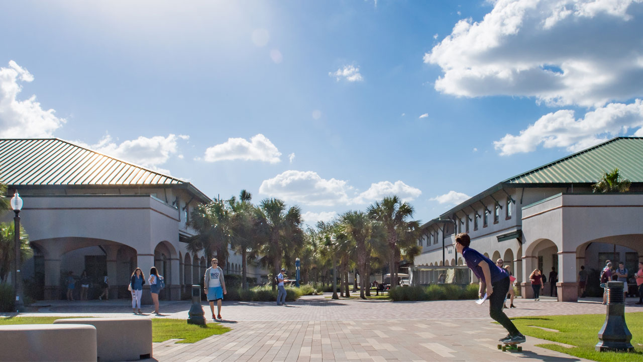Photo of campus with students skate boarding