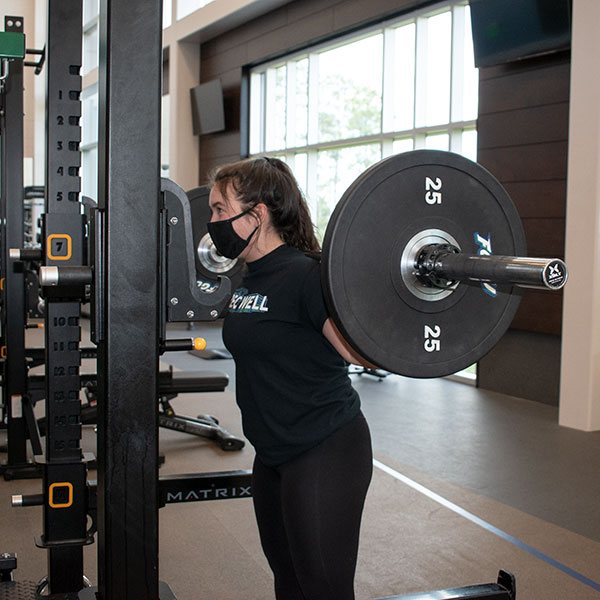 person squatting with bar on weightroom floor